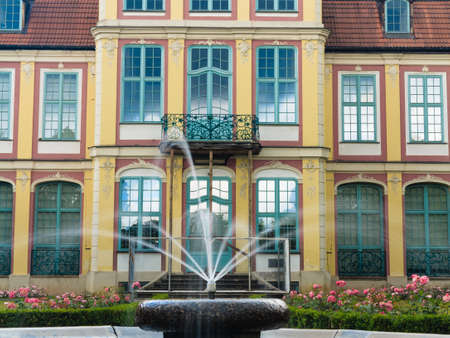famous building: abbots palace landmark in gdansk danzig oliva park poland. famous building with fountain in garden. historical residence house.