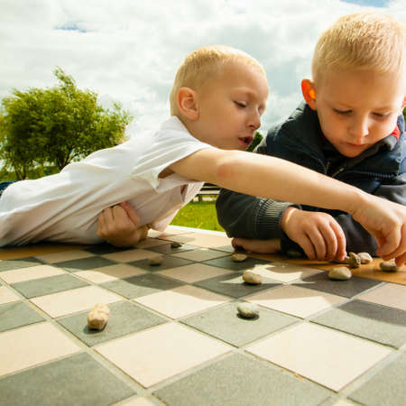 draughts: Draughts board game. Little boys clever children  kids playing checkers thinking, outdoor in the park. Childhood and development
