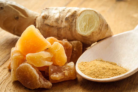 upset stomach: Three kinds of ginger - ground spice fresh and candied on rustic table. Healthy eating, home remedy for nausea upset stomach colds.