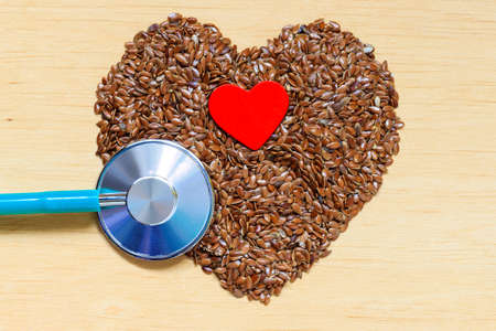 Diet healthcare and checkup concept. Raw flax seeds linseed heart shaped and stethoscope. Healthy food for preventing heart diseases. Stock Photo