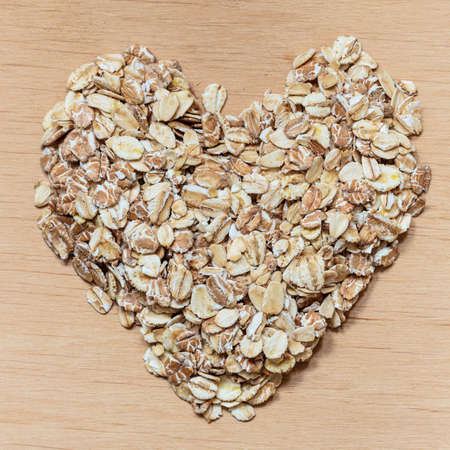 Dieting healthcare concept. Oat cereal heart shaped on wooden surface. Healthy food for lowering cholesterol, protect heart. photo