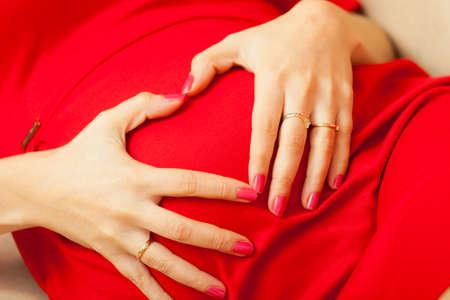 haciendo el amor: El embarazo, la maternidad y el concepto de la felicidad. Hermosa mujer embarazada con estilo elegante en un vestido rojo de relax en el sofá, haciendo forma de corazón con las manos sobre el vientre, símbolo del amor