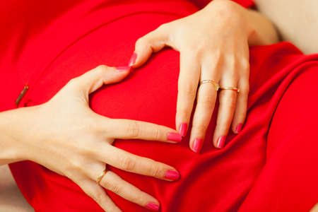 Pregnancy, motherhood and happiness concept. Beautiful stylish elegant pregnant woman in red dress relaxing on sofa, making heart shape with hands over belly, symbol of love photo