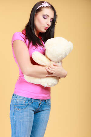 longing: Portrait of childish young woman with headband holding toy. Infantile girl in pink hugging kissing teddy bear on orange. Longing for childhood. Studio shot.