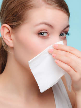 grippe: Flu cold or allergy symptom. Sick woman girl sneezing in tissue on blue. Health care.