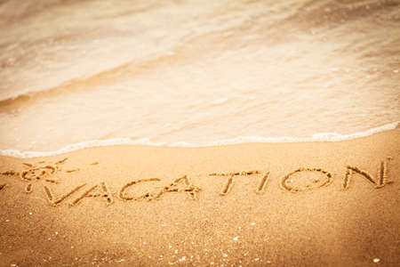 Holidays summer concept. The word vacation written in the sand on beach. photo