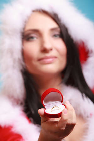 happy girl young woman wearing santa claus costume opening present red heart shaped gift box with engagement ring on blue background. Christmas time gifts. photo