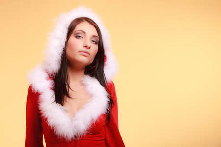 Beautiful sexy woman wearing santa claus costume clothes on yellow background photo