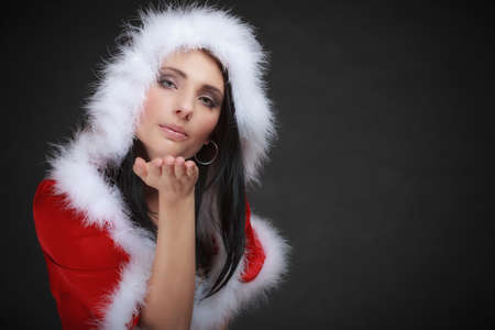 Beautiful sexy woman wearing santa clause costume clothes blowing a kiss on black background photo