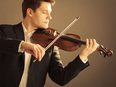 violin player: Art and artist. Young elegant man violinist fiddler playing violin on brown. Classical music.