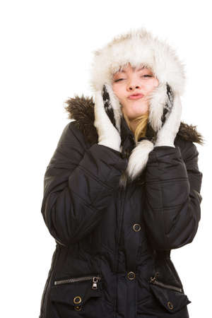 Winter vacation. Cheerful positive girl in warm clothes. Happy young woman in fur hat blowing a kiss isolated on white. photo