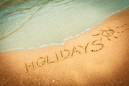 Summer vacation concept. The word holidays written in the sand on beach. photo