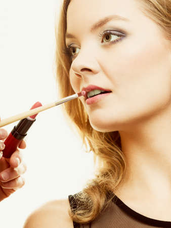 applicator: Cosmetic beauty procedures and makeover concept. Makeup artist applying lipstick with accessories tools to woman lips.