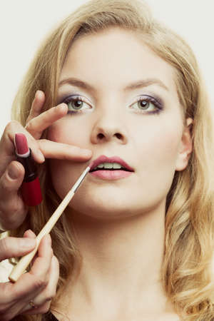makeover: Cosmetic beauty procedures and makeover concept. Makeup artist applying lipstick with accessories tools to woman lips.