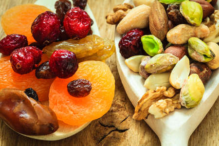 Healthy food organic nutrition. Closeup different varieties mix of dried fruits and nuts on wooden spoons. photo