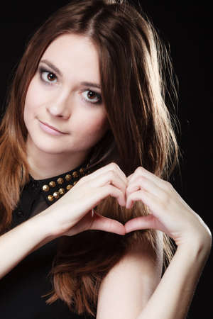 Love valentines day concept. Woman teen girl doing forming heart shape love symbol with her hands on black photo