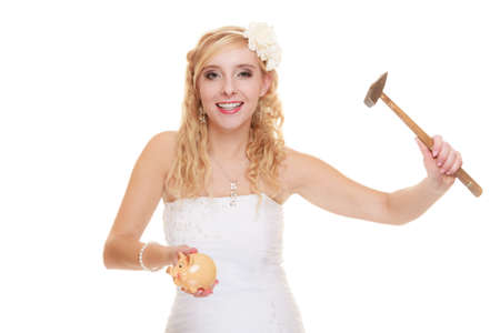 Money saving, marriage and high wedding cost concept. Funny woman bride with hammer about to smash piggy bank isolated on white photo