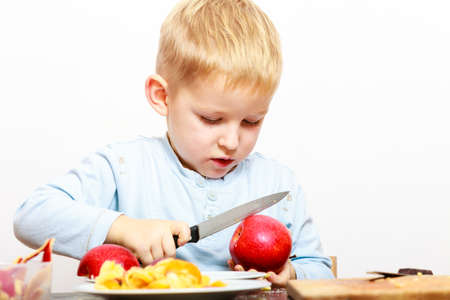 christmas baker's: Child little boy playing dangerous game with a kitchen knife cut apple, making salad at home.