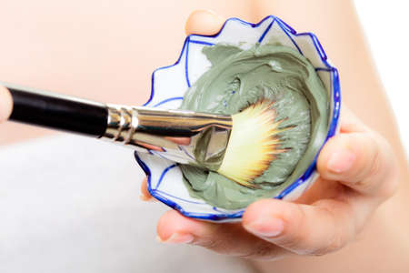 Skin care. Closeup of cosmetic. Woman with brush applying clay mask on face. Girl taking care of dry compexion. Spa. photo