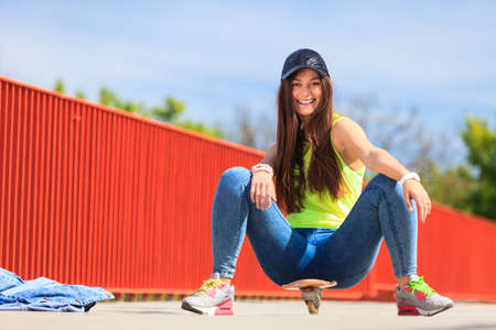 summer sport: Summer sport and active lifestyle. Cool teenage girl skater sitting on skateboard on the street. Outdoor.