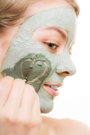 wellfare: Skin care. Woman in clay mud mask on face with heart on cheek isolated on white. Girl taking care of dry complexion. Beauty treatment. Stock Photo