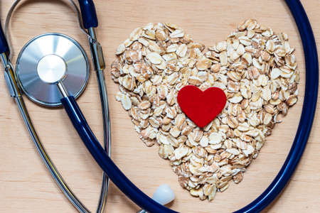 Dieting healthcare concept. Oat cereal heart shaped, stethoscope on wooden surface. Healthy food for lowering cholesterol, protect heart.