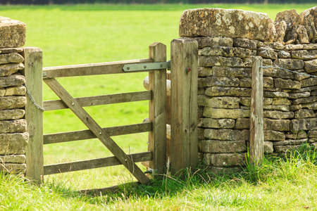 cotswold: Nature summer landscape. Countryside view and rustic gate in drystone wall in village Bibury England, UK. Stock Photo