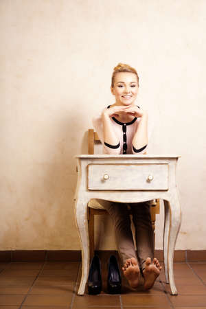 bare foot: Vintage style. Full length of barefoot girl student or businesswoman sitting on the wooden chair at the white retro desk. Design. Stock Photo