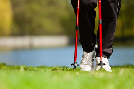 Marcha nórdica. Primer plano de las piernas femeninas de senderismo en el parque. Estilo de vida activo y saludable.