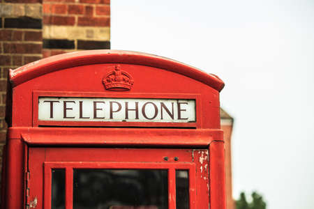 Closeup traditional red telephone box booth or public payphone in England UK photo
