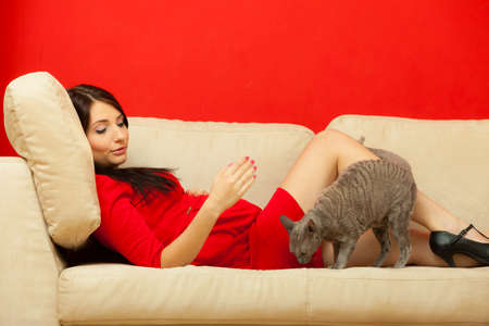 Pregnancy, motherhood and happiness concept. Beautiful elegant pregnant woman in red dress relaxing on sofa playing with cat pet. photo