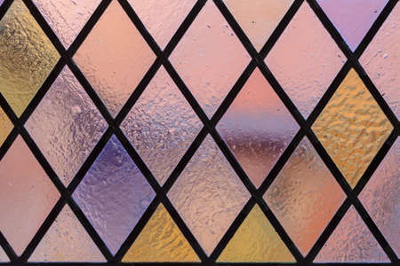 Stained glass with multi colored diamond pattern as background pink violet tone
