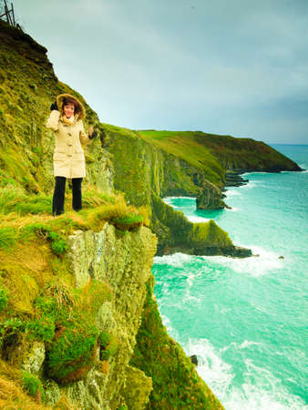 co cork: Woman tourist standing on rock cliff by the ocean Co. Cork Ireland Europe.