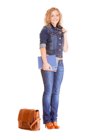 Denim fashion and education. Full length college university student girl with bag books, casual woman in stylish blue jeans pants and jacket high heels. Isolated on white background photo