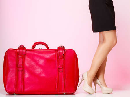 Side view woman legs high heels with old red suitcase on pink background. Elegant lady in voyage, travel concept. photo