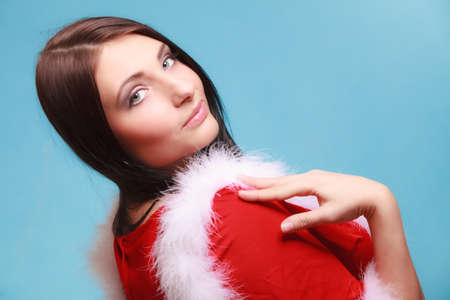 Beautiful sexy woman wearing santa claus costume clothes on blue background photo