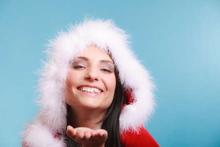 Beautiful happy woman wearing santa clause costume clothes blowing on hand sending a kiss on blue background photo