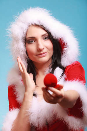 Surprised happy girl young woman wearing santa claus costume opening present red heart shaped gift box with engagement ring on blue background. Christmas time gifts. photo