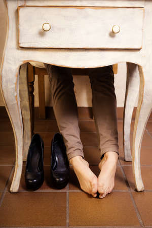 no heels: Bare female feet under the white vintage retro table. Tired businesswoman woman girl with leg cramps relaxing no high heels.