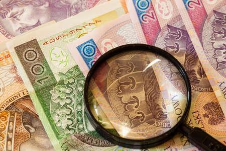 vals geld: Vals geld concept. Poolse zloty bankbiljetten munt en vergrootglas Stockfoto