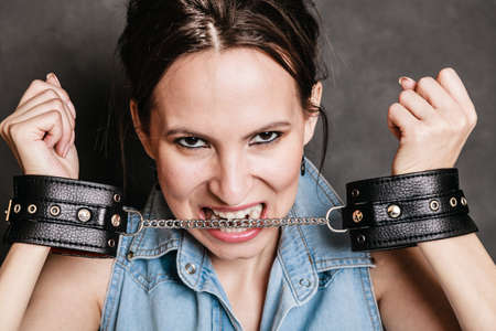 sadomasochism: Arrest and jail. Criminal angry woman prisoner girl showing leather handcuffs on gray. Punishment. Stock Photo