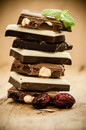 Closeup stack of different sorts chocolate pieces and cranberry. Variety of chocolates on wooden table. photo
