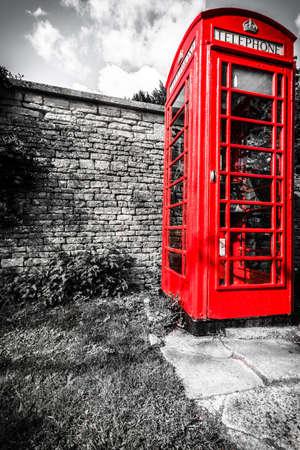 Traditional red telephone box booth or public payphone, village Bibury England UK photo