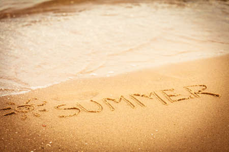 Holidays vacation concept. The word summer written in the sand on beach. photo