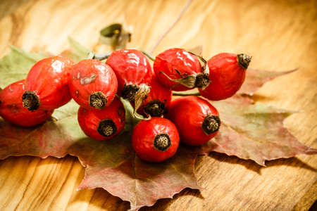 Hawthorn and maple leaf on wooden rustic table background. Rose hips haw fruit of the dog rose. photo