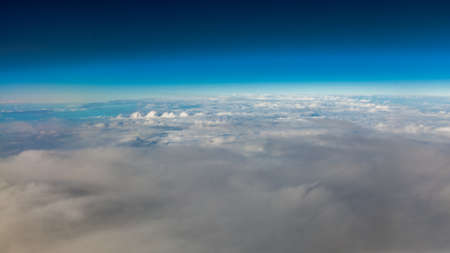 skyscape: Blue sky. View from window of airplane flying in clouds. Skyscape cloudscape. Birds eye.