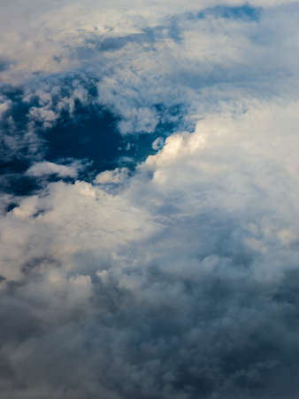 skyscape: Blue white cloudy sky. View from window of airplane flying in clouds. Skyscape cloudscape. Birds eye. Stock Photo
