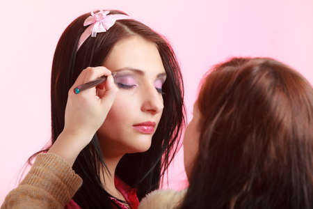 visagiste: Female beauty. Makeup artist stylist applying with brush violet purple eyeshadow on eyelid of young woman on pink. Girl by visagiste.