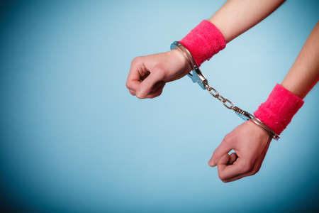 cuffed: Teen crime, arrest and jail - Hands of criminal teenager girl prisoner woman in handcuffs blue background Stock Photo