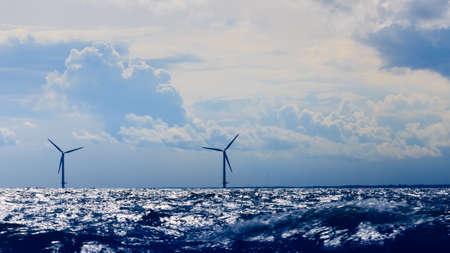 resource conservation: wind turbines power generator farm for renewable energy production along coast baltic sea near Denmark. Alternative green energy ecology.